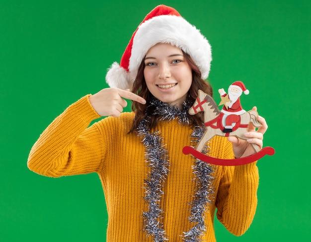 サンタの帽子と首の周りに花輪を持って、コピースペースで緑の背景に分離されたロッキングホースの装飾でサンタを指差して喜んでいる若いスラブの女の子 無料写真