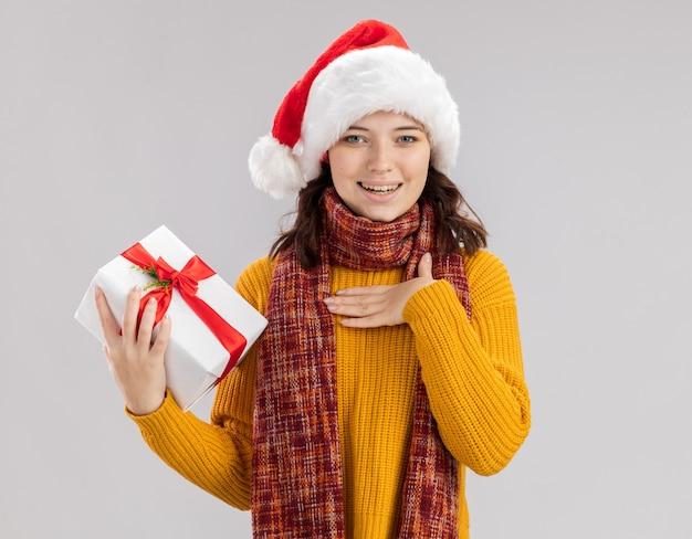 サンタの帽子と首にスカーフを持って喜んで若いスラブの女の子は胸に手を置き、コピースペースで白い背景で隔離のクリスマスギフトボックスを保持します。 無料写真