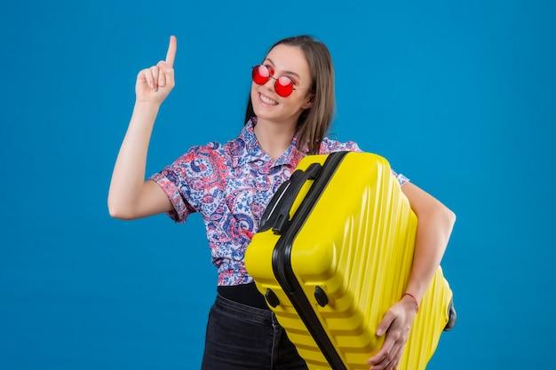 青い背景に素晴らしいアイデアを持っていると自信を持って探しているを指で立っている黄色のスーツケースを持って赤いサングラスをかけている満足している若い旅行者女性 無料写真