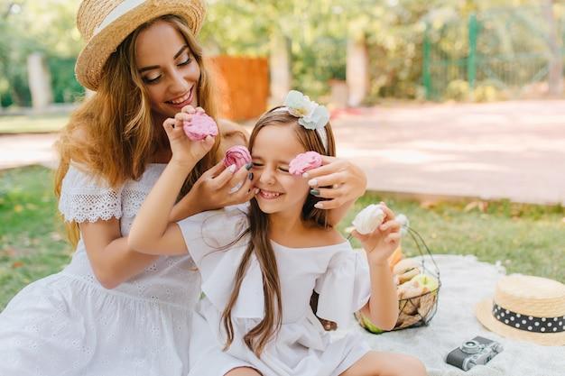 果物のバスケットと毛布の上に座っている白い服装の若い女性と興奮した女の子を喜ばせます。昼食時に娘と浮気する優雅な女性の屋外写真。 無料写真
