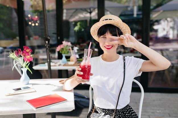 Lieta giovane donna in cappello di paglia in posa con il segno di pace, tenendo in mano un bicchiere di bevanda fredda in mattinata estiva Foto Gratuite