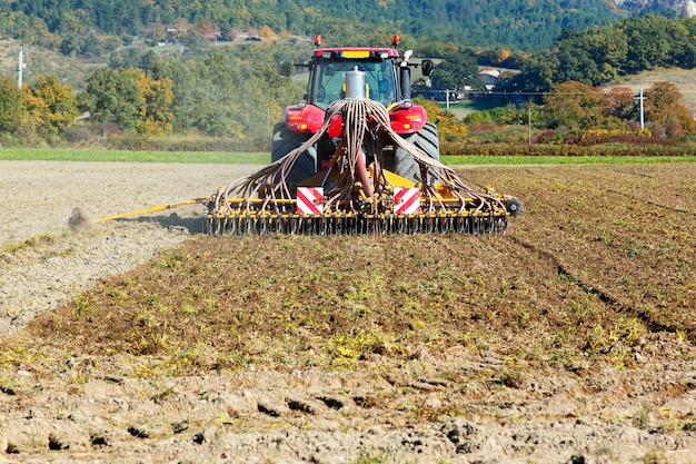 Ploughing heavy tractor during cultivation agriculture works at field with plough Free Photo