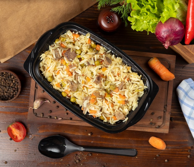Plov, rice garnish with vegetables, carrots, chestnuts and beef pieces Free Photo