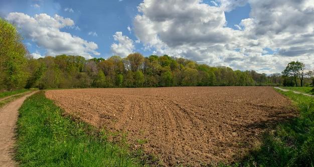 Вспаханное поле и голубое небо с облаками Premium Фотографии