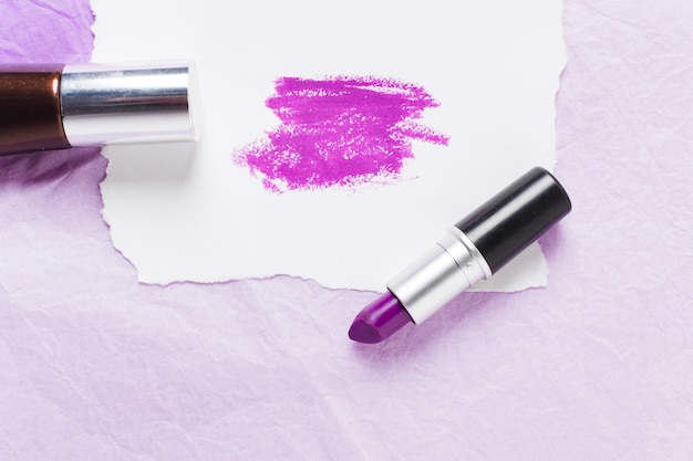 Plum lipstick with smears on paper sheet and nail polish Free Photo