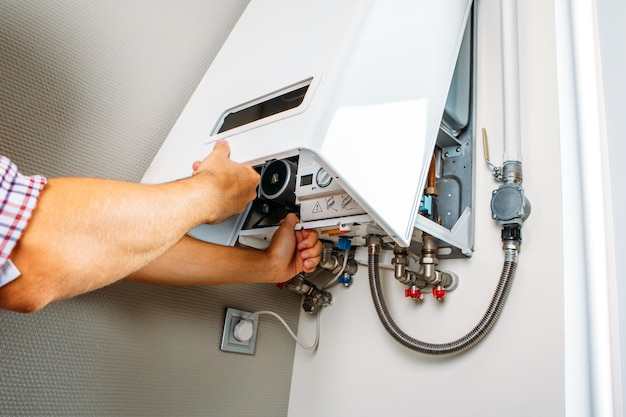 Plumber attaches trying to fix the problem with the residential heating equipment. repair of a gas boiler Premium Photo