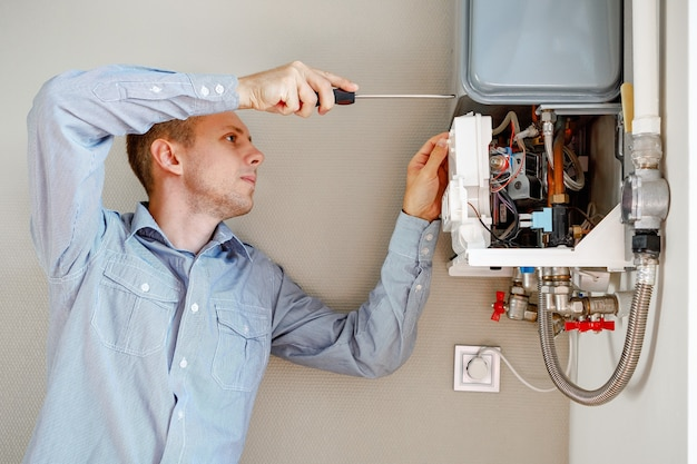 Plumber attaches trying to fix the problem with the residential heating equipment Premium Photo