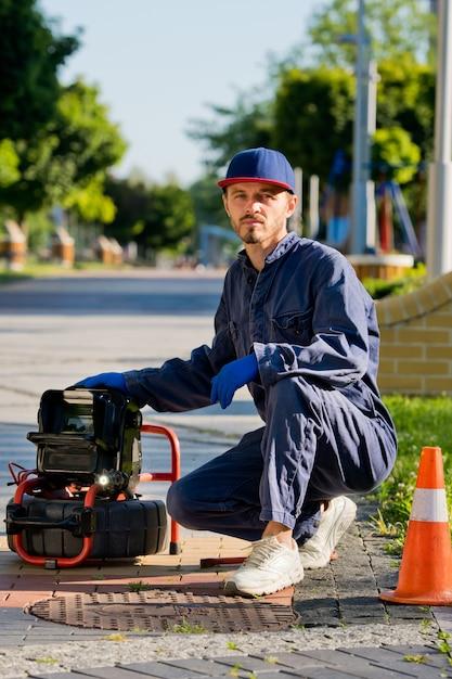 配管工は、特別な機器を使用して、路上で排水溝をよく診断します。 Premium写真