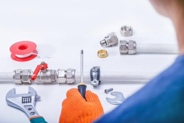 A plumber fixes a water leak on a water pipe Premium Photo