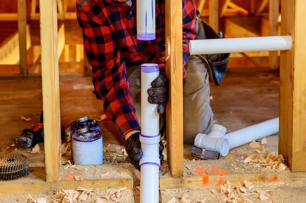 配管工の接着剤の白いpvcパイプ、新しい家に新しいプラスチックの排水管を取り付ける Premium写真