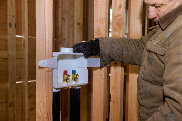 新しい家庭用品洗濯機で洗濯コンセントボックスを設置する配管工 Premium写真