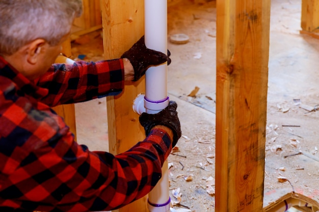 Plumber installing pvc pipe at under construction of the house Premium Photo