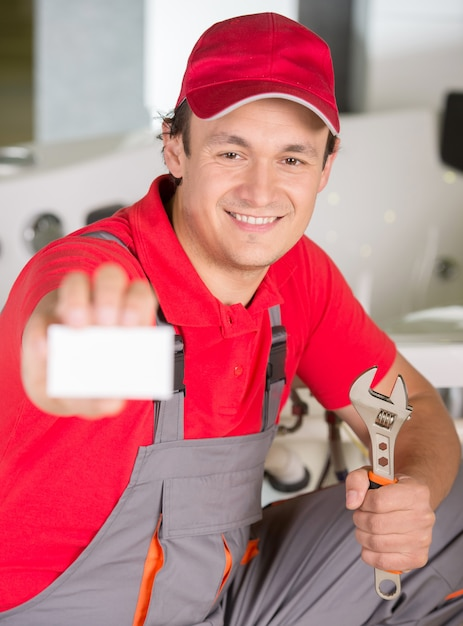 Plumber is holding spanner in hand and showing business card Premium Photo