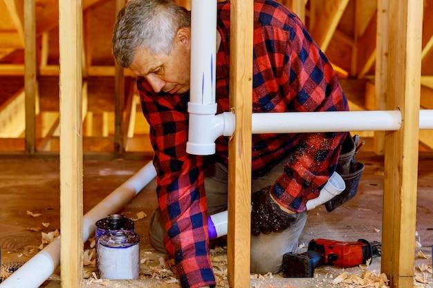 建設中の新しい家の下で排水管用の接着剤でプラスチックパイプを結合する配管工 Premium写真