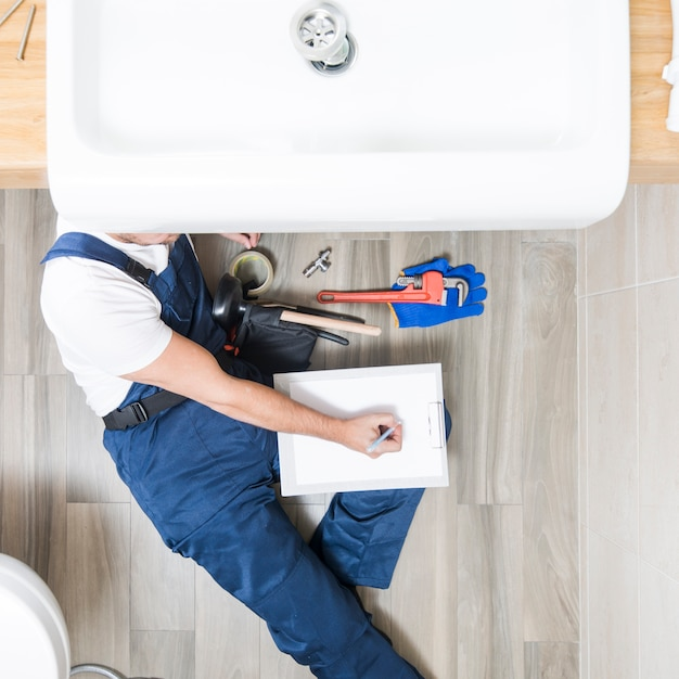 Plumber lying and writing in tablet Premium Photo