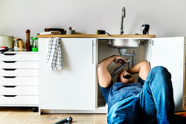 Plumber man fixing kitchen sink Free Photo