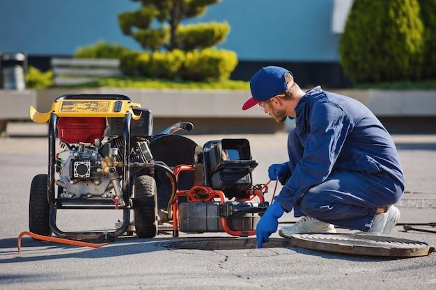 配管工は下水道の問題を解決する準備をしています。トラブルシューティングの修復作業。 Premium写真
