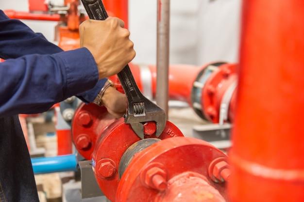 Plumber repairing and performing maintenance big water pipes. Premium Photo