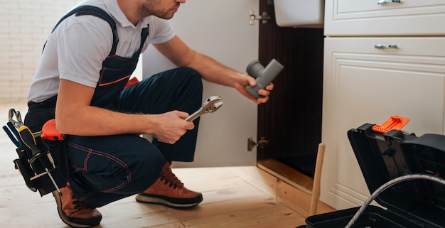 Plumber sitting in squad position in kitchen Premium Photo
