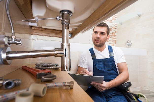 Plumber with tablet repairing sink Premium Photo