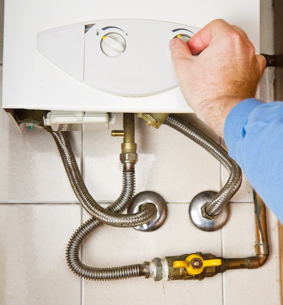 Plumber at work. servicing gas boiler Premium Photo