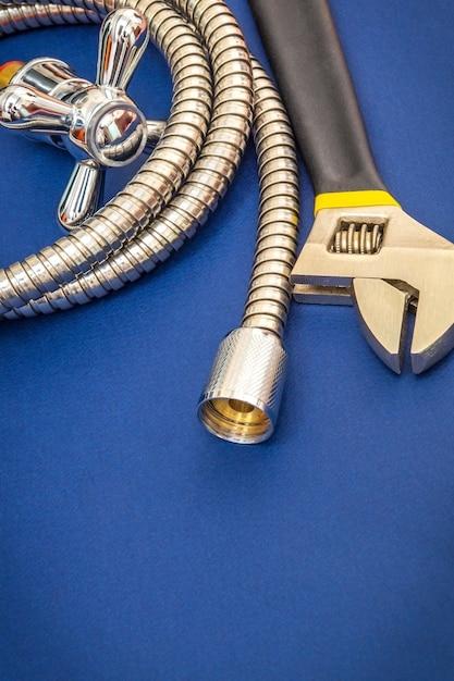 Смеситель, инструмент и шланг для сантехнических материалов на синем фоне используются для замены в душе Premium Фотографии