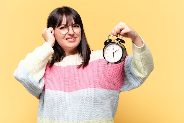 Plus size pretty woman with an alarm clock Premium Photo