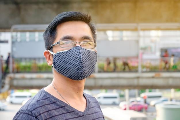 Мужчина в очках и черной маске для рта против загрязнения воздуха с pm 2.5 в бангкоке, таиланд Premium Фотографии