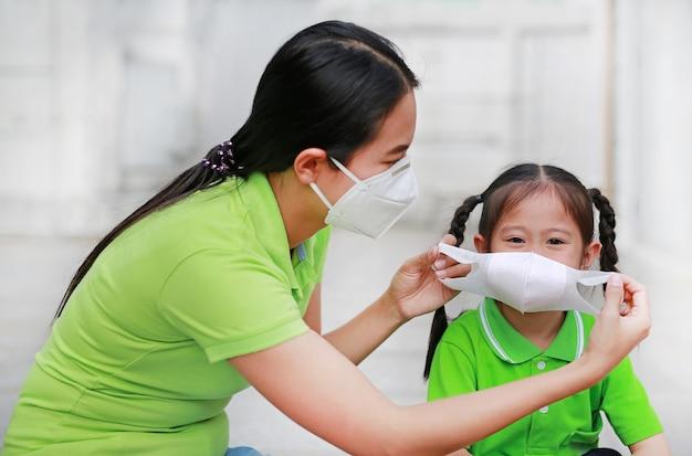 Азиатская молодая мать нося защитную маску для ее дочери пока снаружи к против загрязнения воздуха pm 2,5 в городе бангкока. таиланд. Premium Фотографии