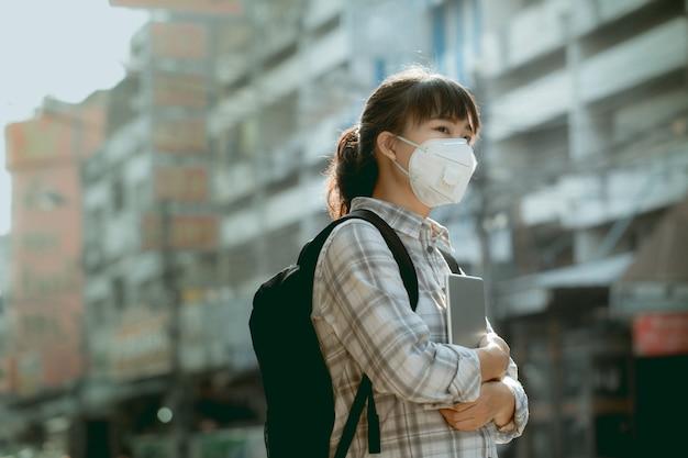 Азиатская девушка студента в маске от пыли pm 2.5 в городе, полном пыли и дыма. Premium Фотографии