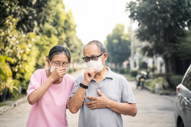 Маска азиатских старших старших пар нося для предотвращает pm сумерк 2.5 плохое загрязнение воздуха. Premium Фотографии