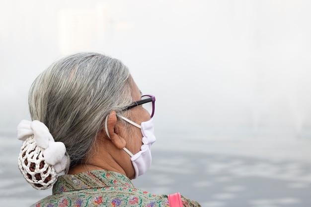 Старая женщина нося маску pm2.5 защищает коронавирус, пыль опасности в бангкоке юго-восточной азии Premium Фотографии