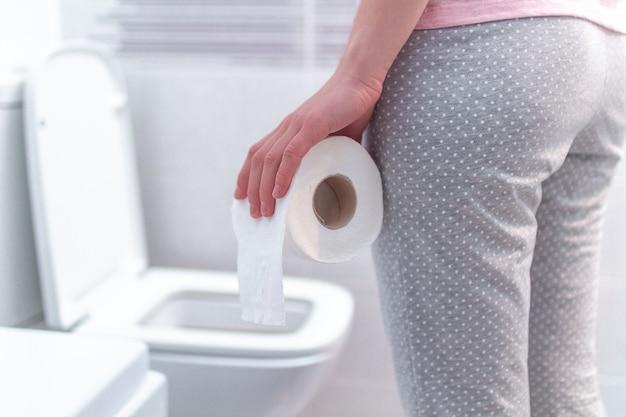 ロール紙を保持し、トイレで下痢、便秘、膀胱炎に苦しんでいる女性。 pms中の胃の痛み。健康管理 Premium写真