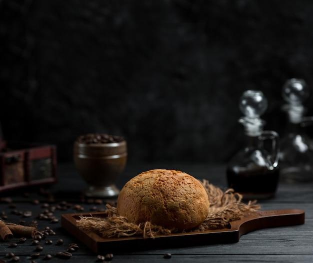 非常に暗い空間で丸い前菜パンpn木の板 無料写真