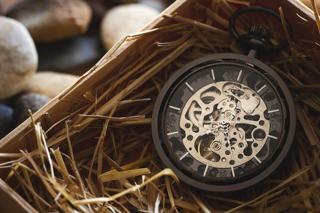 Pocket watch winder on natural wheat straw in a wooden box. Premium Photo