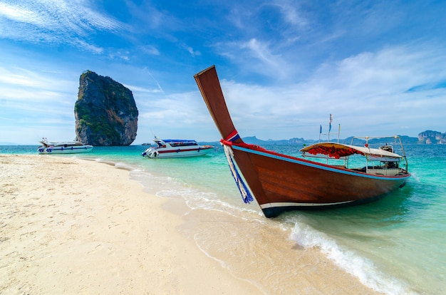 Poda island wooden boat parked on the sea, white beach on a clear blue sky Premium Photo