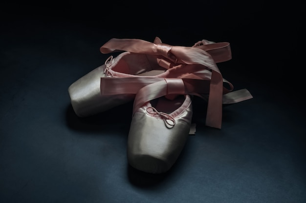 Pointe shoes ballet dance shoes with a bow of ribbons beautifully folded on a dark background. Premium Photo