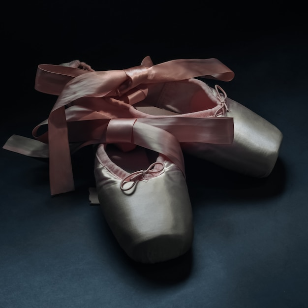 Pointe shoes ballet dance shoes with a bow of ribbons beautifully folded on dark Premium Photo