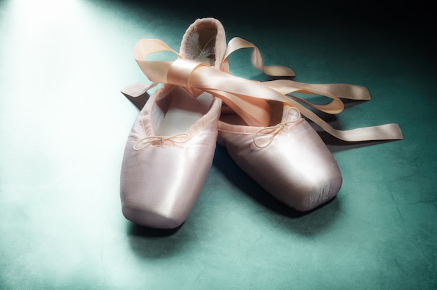 Pointe shoes ballet dance shoes with a bow of ribbons beautifully folded on green Premium Photo