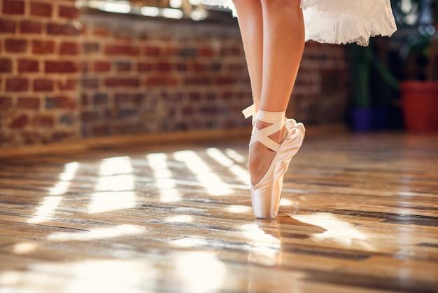 Ноги танцы конца-вверх балерины нося белые ботинки балета pointe в танцевальном зале. Premium Фотографии