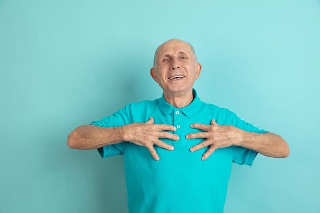 Puntando su se stesso. ritratto dell'uomo maggiore caucasico sullo studio blu. Foto Gratuite