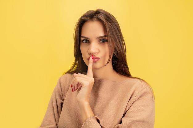 ポインティング。黄色で隔離の若い白人女性の肖像画 無料写真