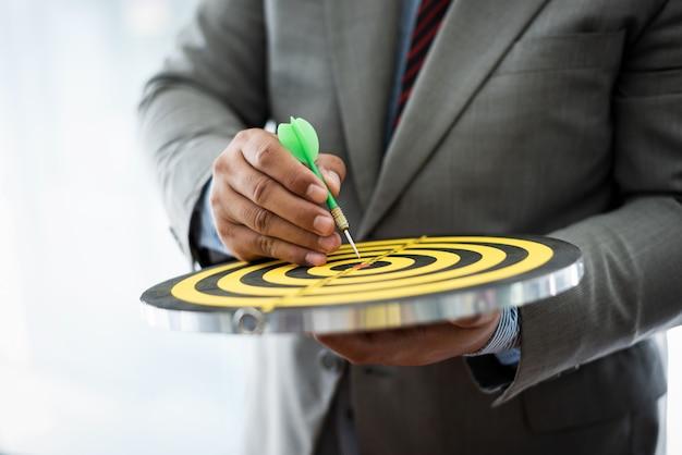 吸引の概念のためのダーツボードの中心にpoitingビジネスの男性。 Premium写真
