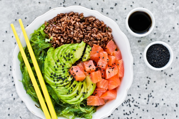 Poke bowl. ingredients: salmon, avocado, brown rice, algae. Premium Photo
