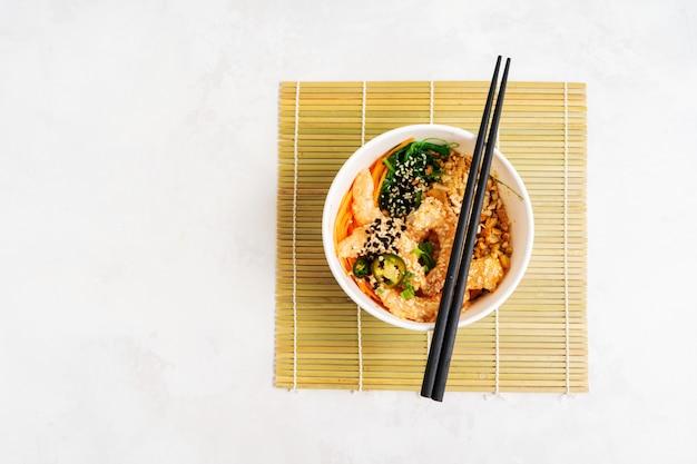 Азиатская предпосылка еды с пряным шаром poke креветки с рисом, морскими водорослями и семенами сезама, авокадоом с палочками на белизне. чаша будды. здоровый обед из морепродуктов. диетическое питание. вид сверху с копией пространства. Premium Фотографии