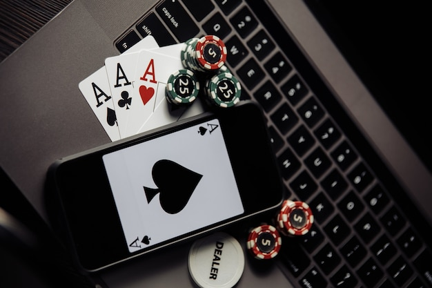Poker chips, cards and smartphone on a grey keyboard. poker online concept Premium Photo