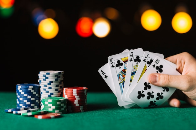 Poker player's hand with royal flush club near chips on green surface Free Photo