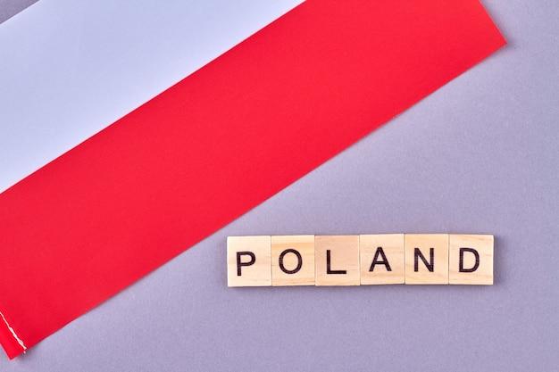 木製のブロックで書かれたポーランド。紫の背景に分離されたヨーロッパの国の国旗。 Premium写真