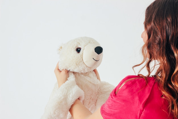 Polar bear toy on hands of young woman in bright pink dress Premium Photo