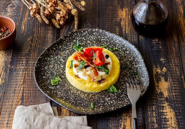 モッツァレラチーズ、ベーコン、トマトのポレンタ Premium写真